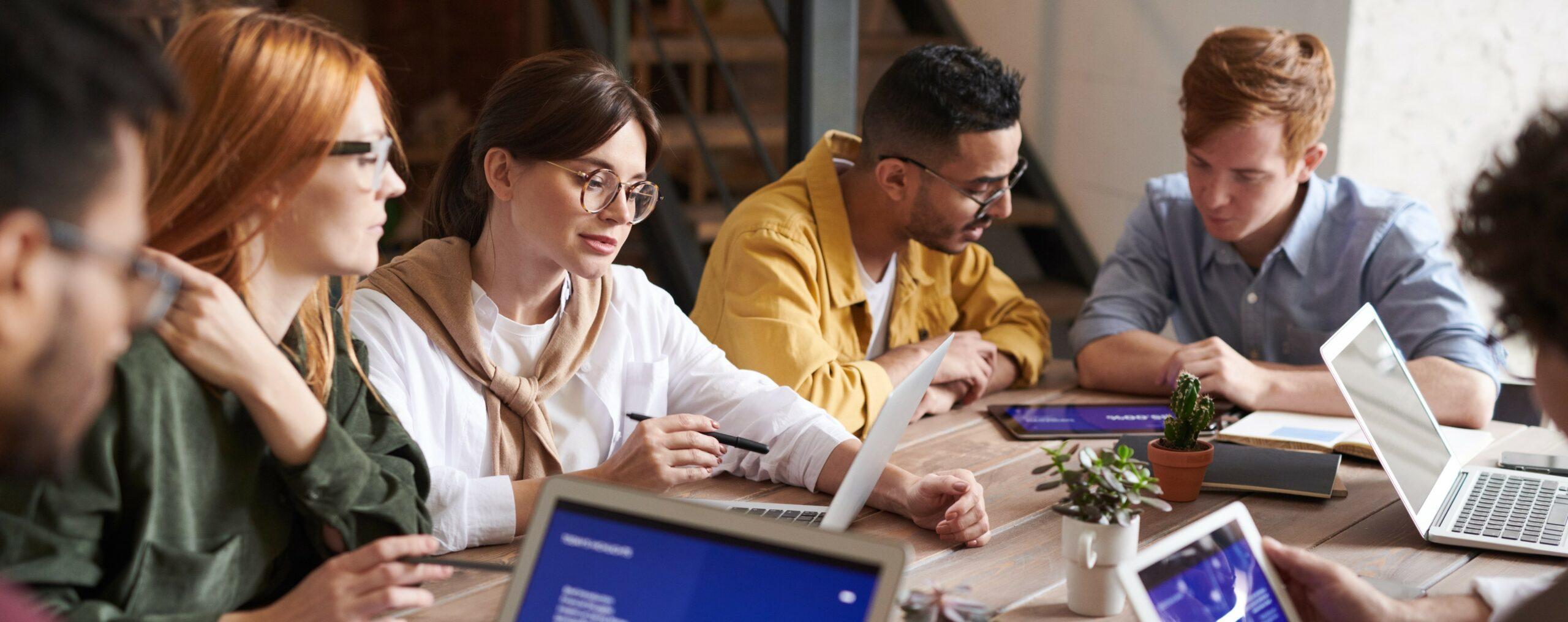 Eine Besprechung, bei der mehrere Personen auf Computer schauen.