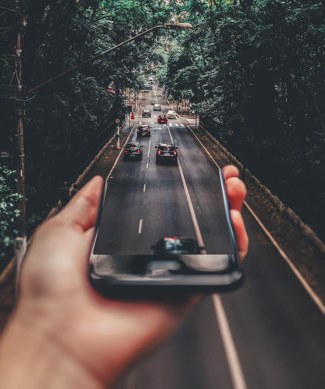Symbolbild innovative Mobilität: Eine Hand hält ein Smartphone aus dem Auto herausfahren.