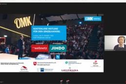 Screenshot der Videokonferenz OMK.digital mit Präsentation und Moderator.