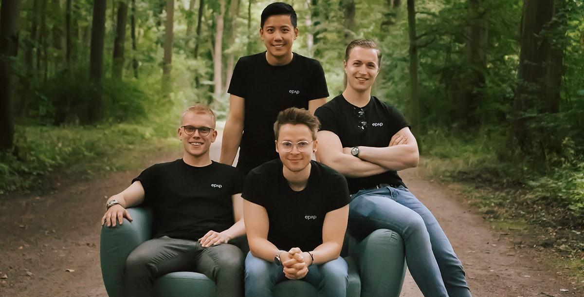 Das Bild zeigt die vier jungen Gründer vom Startup epap., die im Wald auf einem Sofa sitzen.