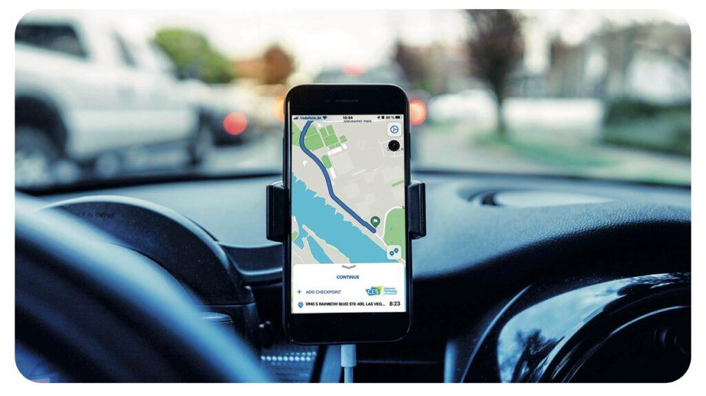 Armaturenbrett im Auto mit Smartphone und Navigationsapp in einer Halterung.