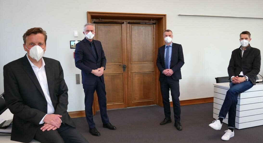 Das Bild zeigt vier Männer die mit Abstand nebeneinander stehen und einen Mundschutz tragen.