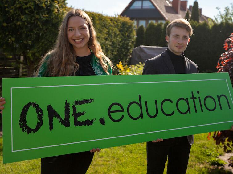 Die Gründerin Laura und der Gründer Joscha stehen im Garten und halten ein großes Schild mit dem Namen ihres Startups One.Education hoch.