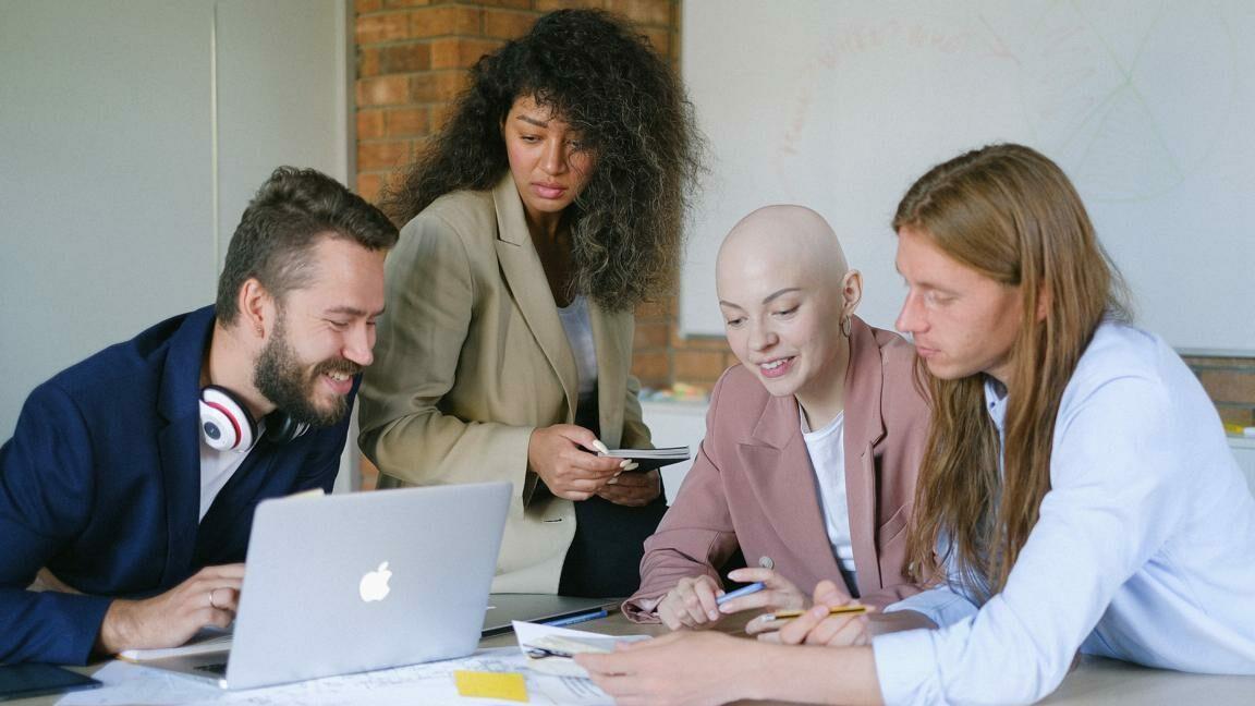 Das Bild zeigt vier diverse Personen, die gemeinsam an einem Schreibtisch sitzen und arbeiten.