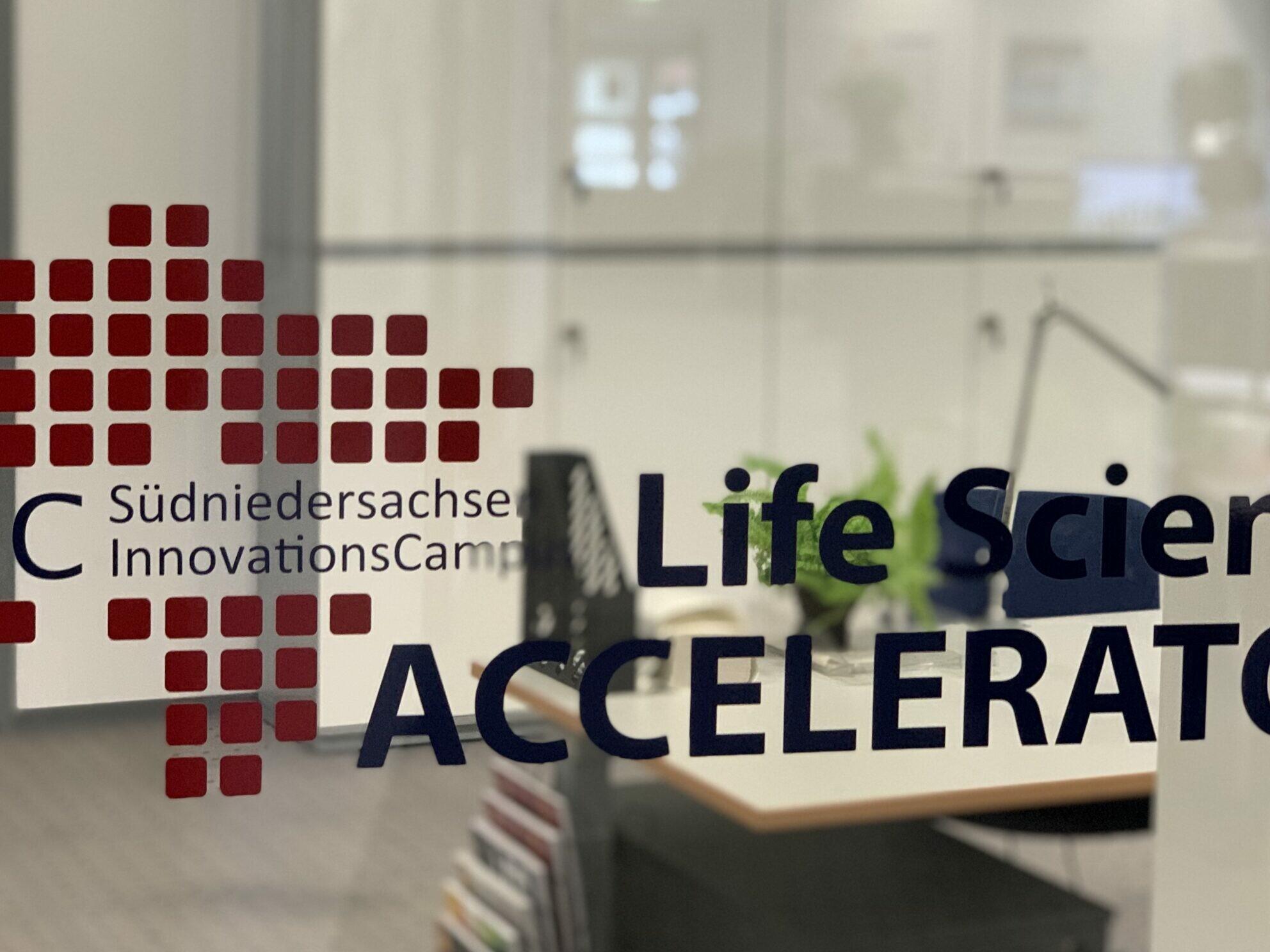 Das Bild zeigt eine Glasscheibe mit dem Logo des SNIC Accelerators. Im Hintergrund sieht man ein Büro.