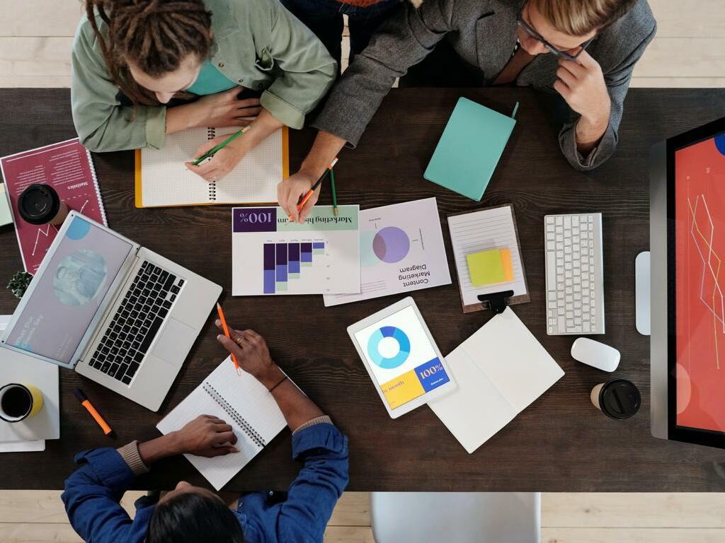 Von oben: Menschen arbeiten an einem Tisch zusammen und erheben Daten.