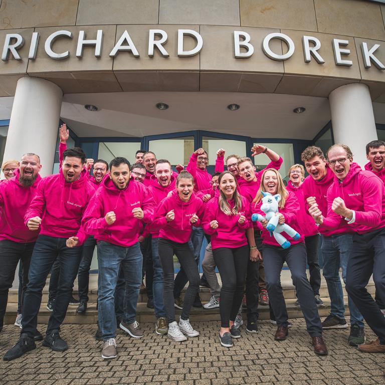 Das Bild zeigt das Team von borek.digital vor ihrem Bürogebäude.